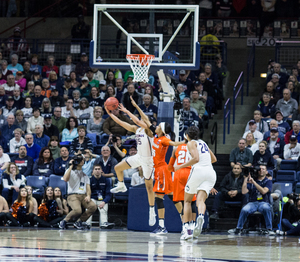 A Connecticut player attempts a reverse layup on Monday night against the Orange. The four-time defending champs Huskies beat SU by 30.