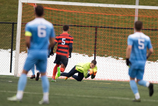 Syracuse goalie Hendrik Hilpert hauls in a ball. He made eight saves in the contest. SU defender Louis Cross looks on.