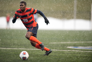 SU defender Kamal Miller runs through the wet conditions.