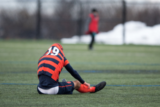 Syracuse defender Miles Robinson sits on the turf with his jersey tucked over his head.