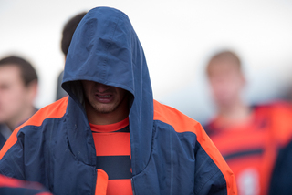 A Syracuse player walks off the field with his hood over his head.