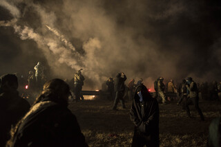 Law enforcement releases tear gas to disperse the crowd of nonviolent water protectors gathered at the barricade on Nov. 20. The barricade, erected three weeks prior when protectors marched toward the pipeline, was being cleared from wreckage when protectors arrived from the nearby camp.